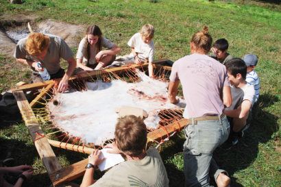 group of students stretching an animal hide